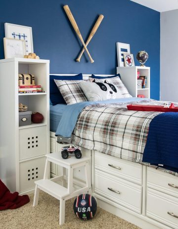 Blue boy's bedroom color scheme with white furniture, tall bed with drawers, blue wall, and baseball bats hanging as art.