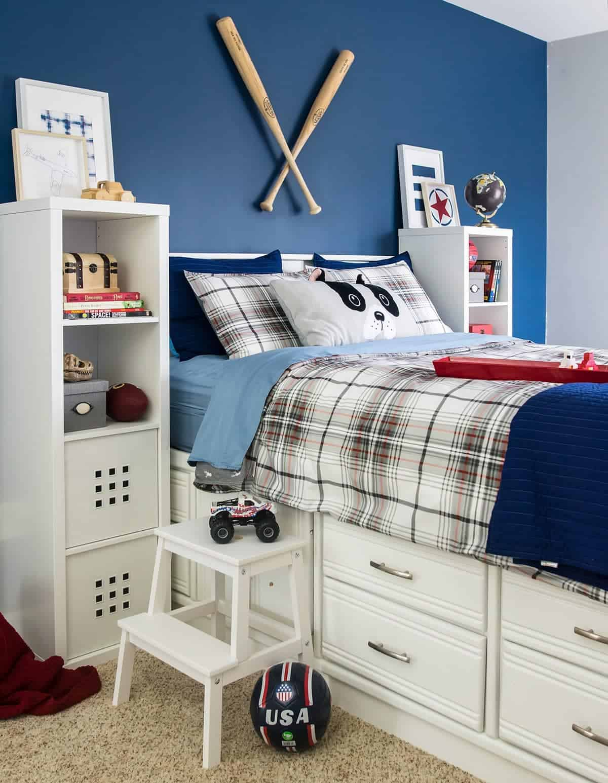 Boy's room after makeover with refinished white captain's bed and step stool with plaid bedding, white lockers, and various sports related decor.