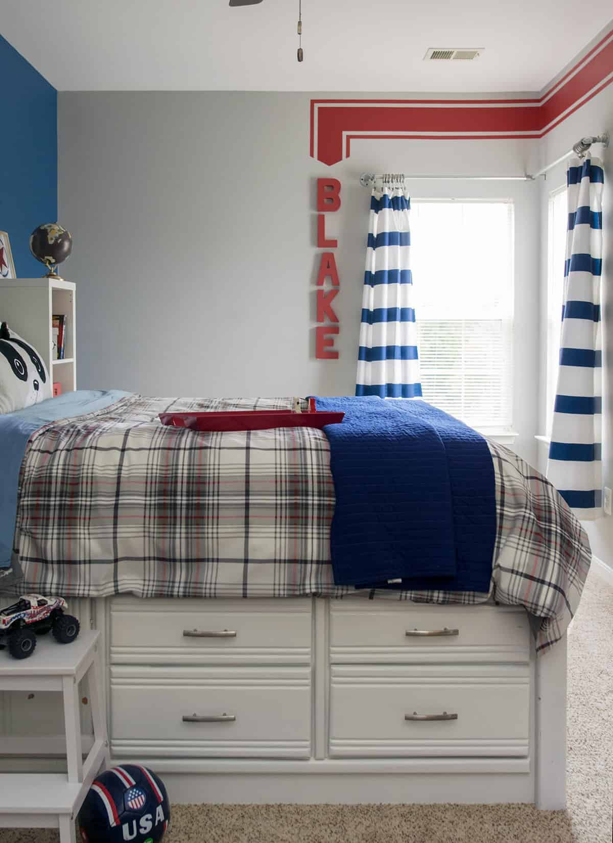 Refinished white captain's bed in little boy's room with plaid comforter and navy blanket. Dark blue and gray walls with personalized red wall stripe.