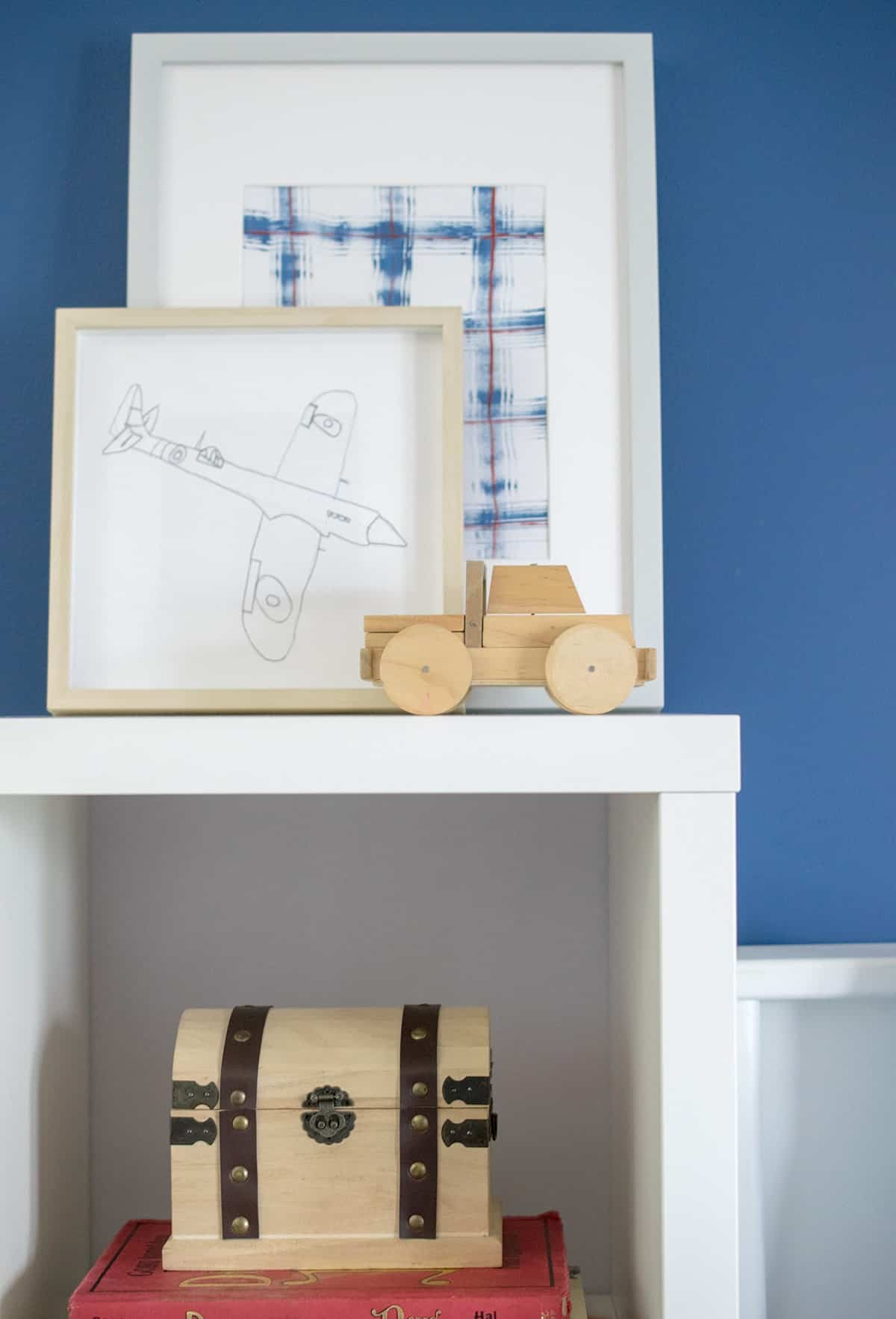 Child's original artwork display on white shelf bedside shelf