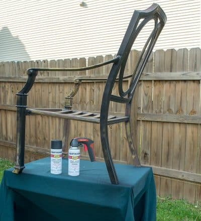 A metal chair on a table prepped for spray painting.