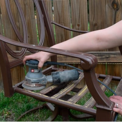 Woman sanding a metal chair with an orbital sander.