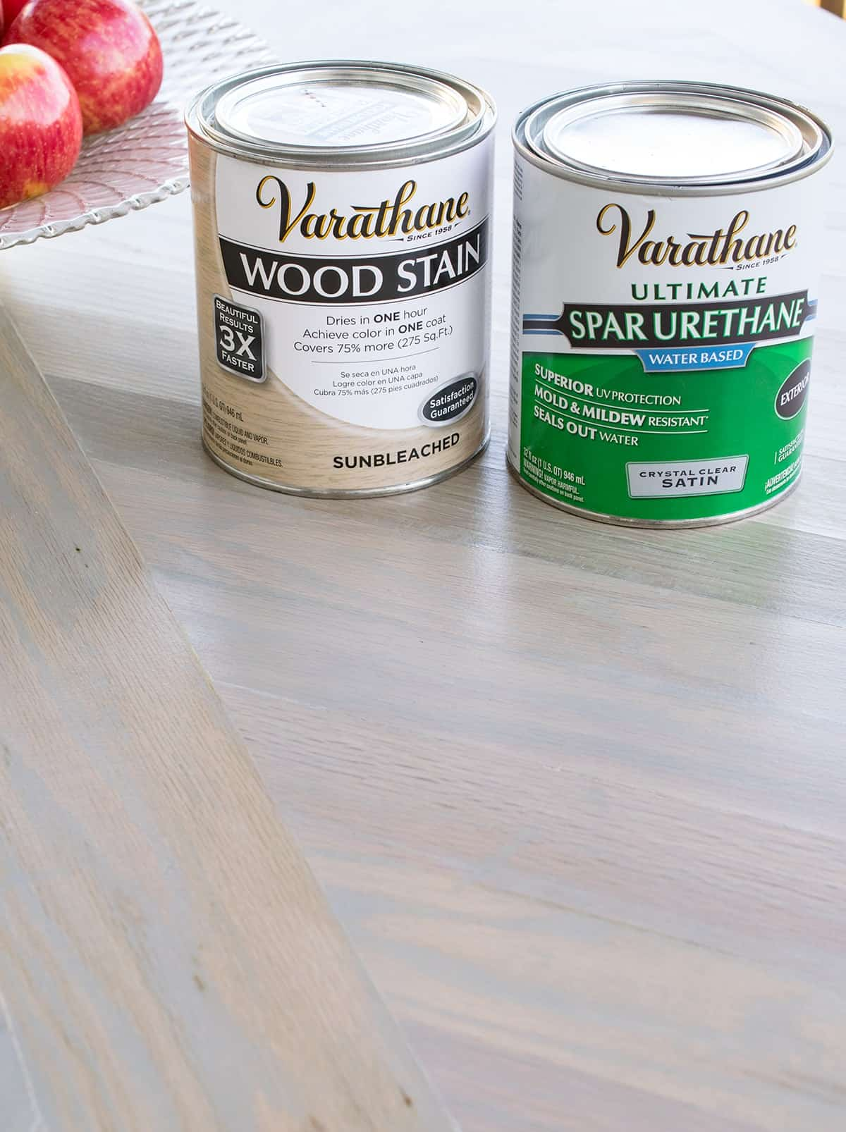 Varathane wood stain and spar urethane product cans on table top with finished product applied.