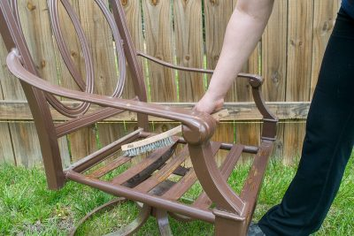 Woman using a wire brush to remove chipping paint from metal chair.