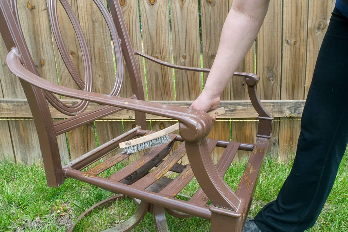 Removing old paint and rust from patio chair using a wire brush.