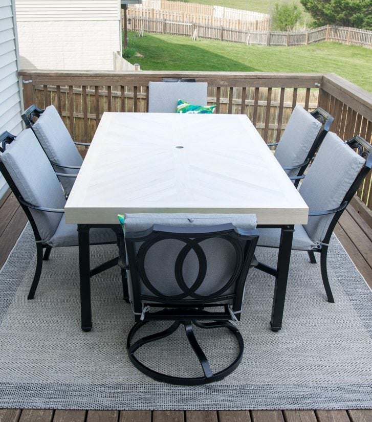 White outdoor table with black chairs on a deck.