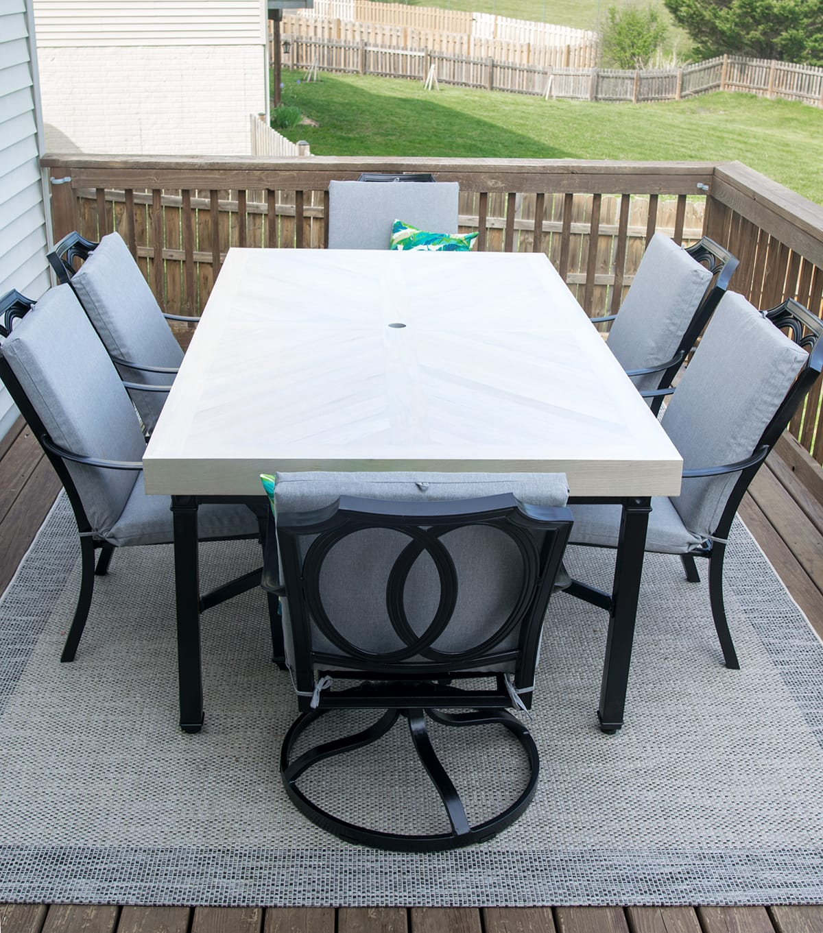 Metal patio table and chairs refinished with black trim, wood top, and gray cushions.