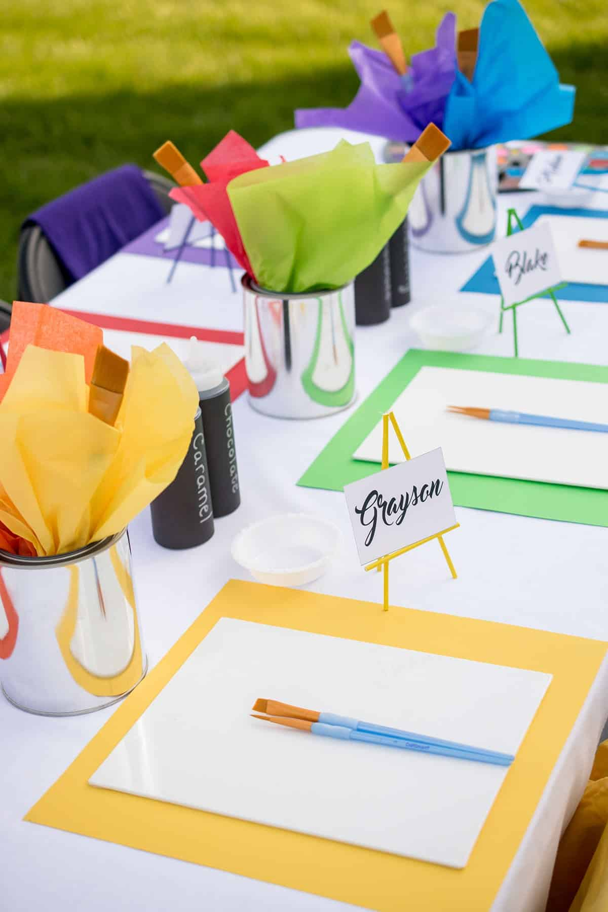 Recycled paint cans with rainbow tissue paper and paint brushes as centerpieces for kid's paint party