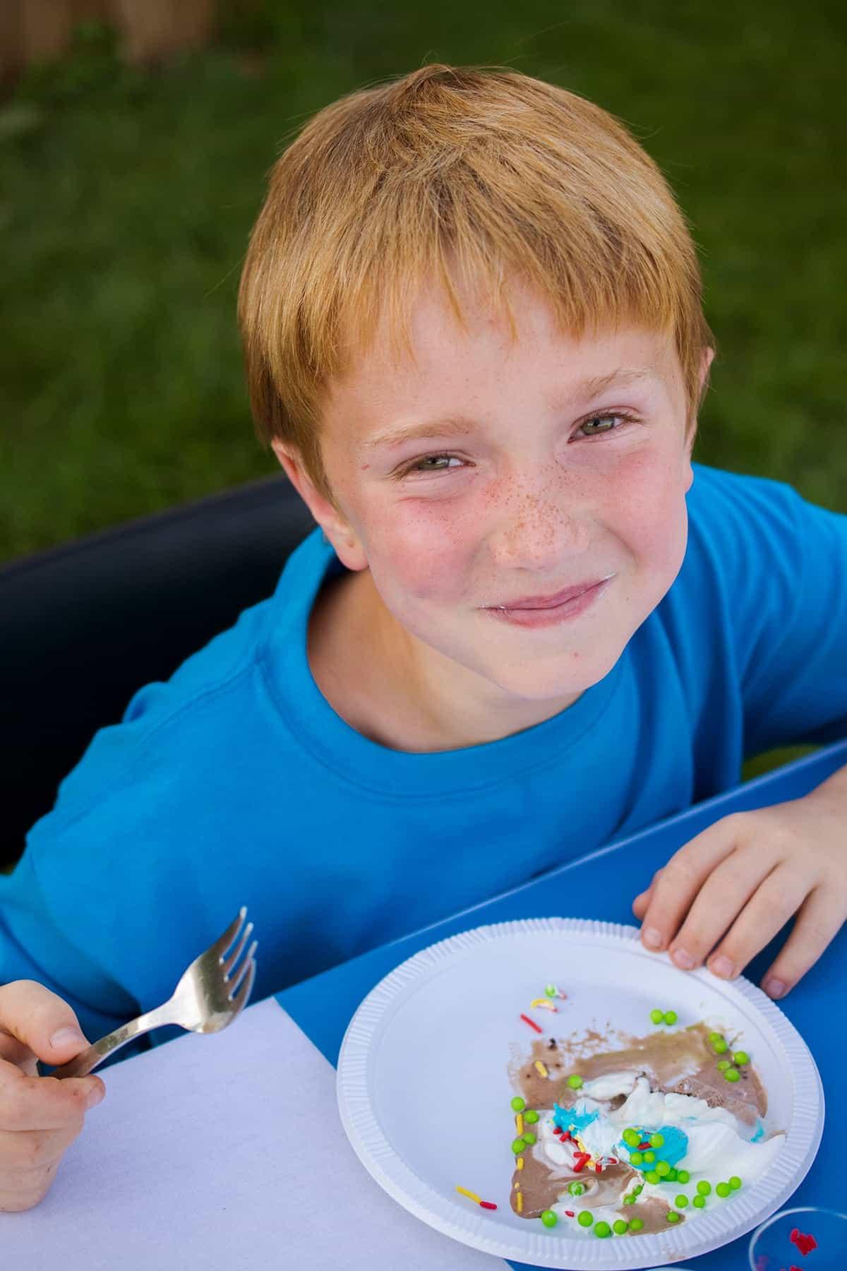 Boy in blue shirt enjoying ice cream cake