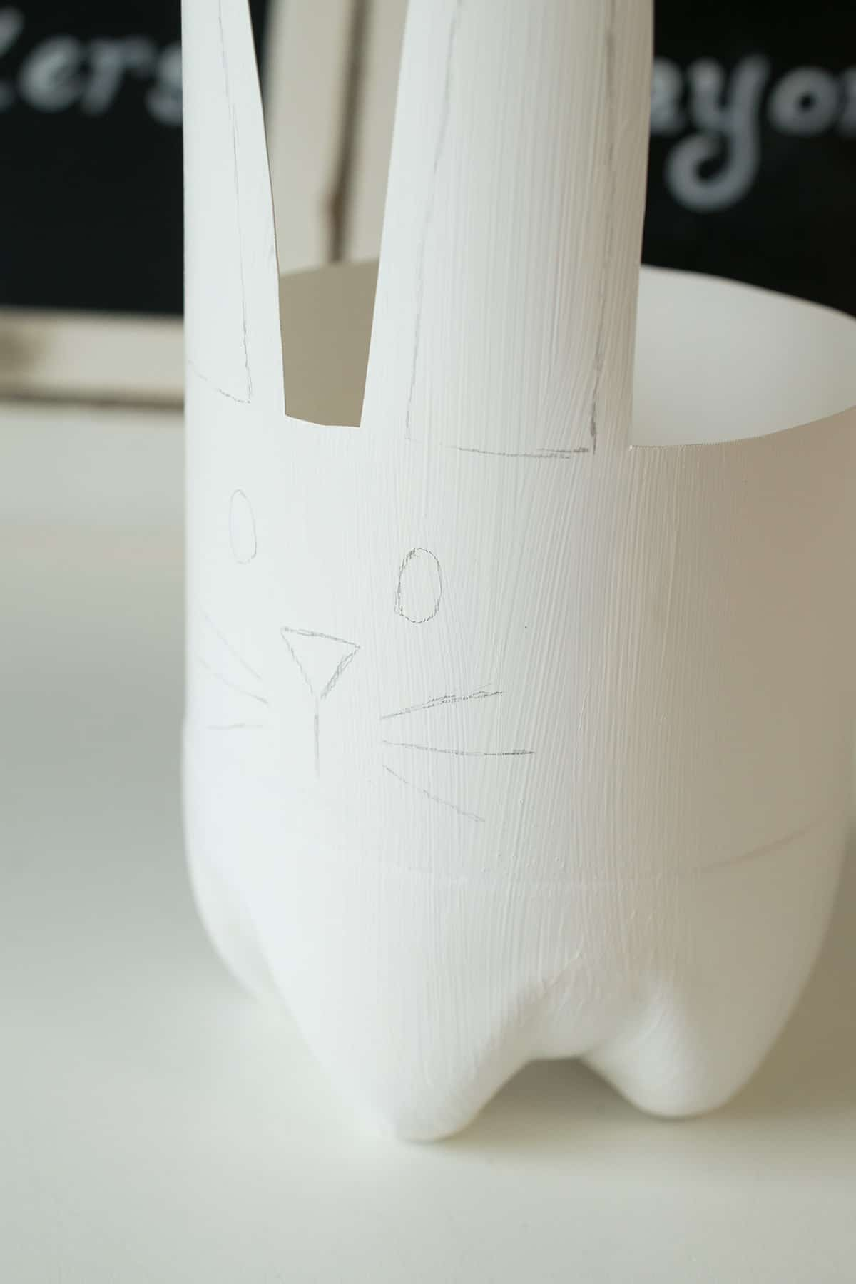 Bottle cut into bunny shape, painted white with face penciled in