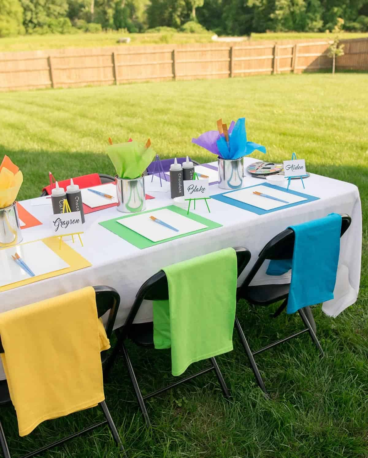 Backyard playdate table setting with rainbow place settings and individual painting supplies