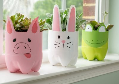 Plastic bottle animal planters on a window sill. Includes a pig, rabbit, and frog planter.