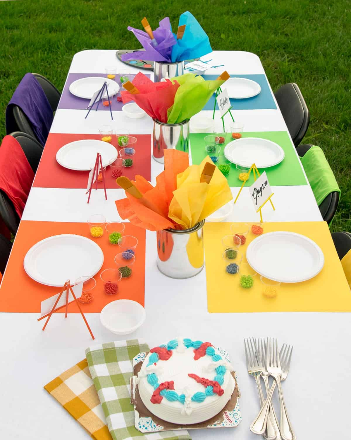 Rainbow outdoor table setting with individual place settings for cake decorating