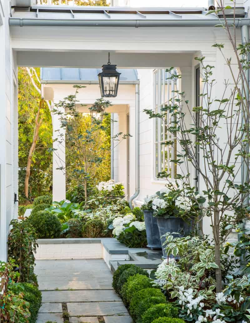 Refreshed home exterior with blooming landscaping, clean patio space.