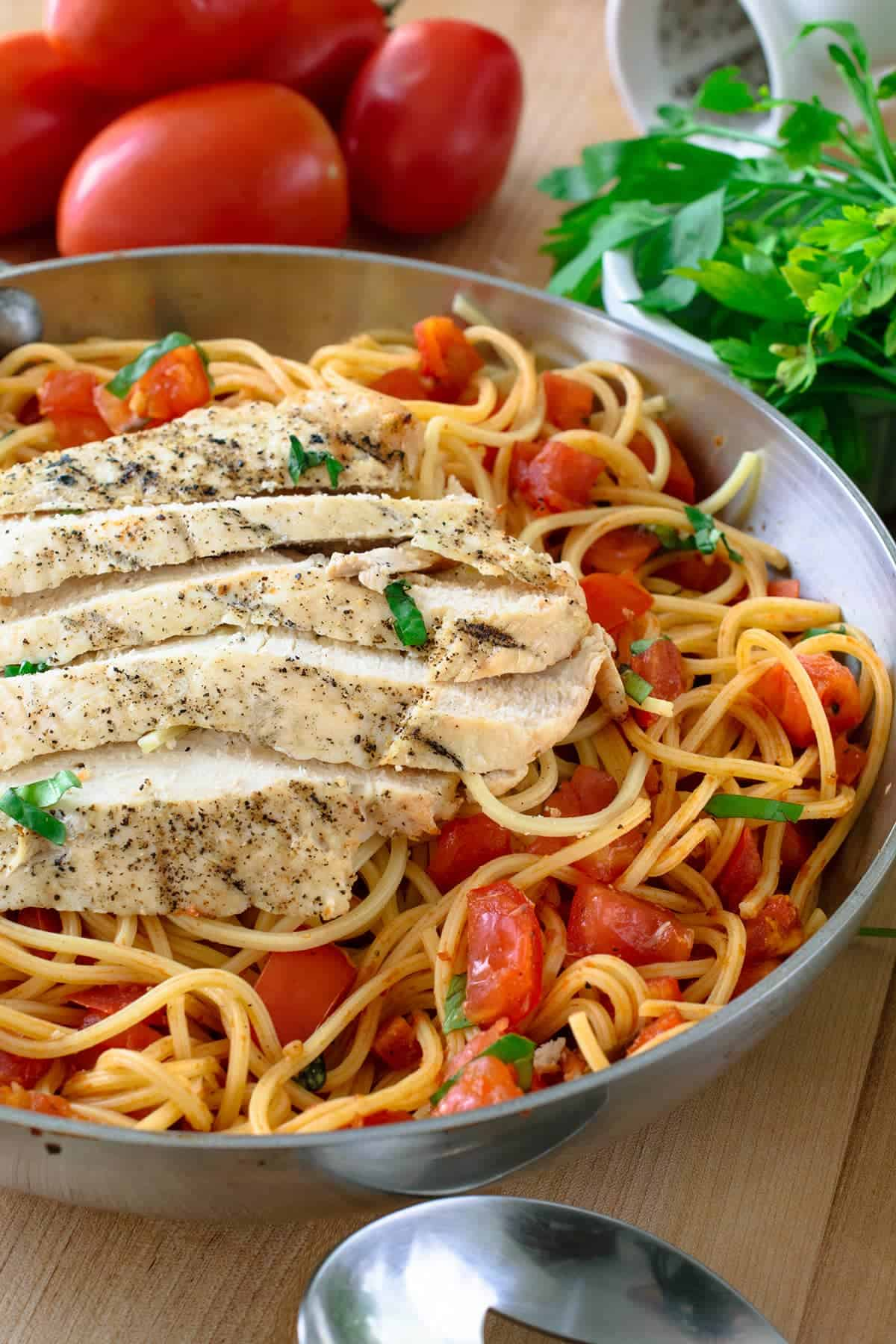Bruschetta Chicken Pasta with tomato and basil, grilled seasoned chicken sliced on top in silver bowl