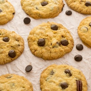 Chocolate Chip Cookies with pecans laid out to cool on wax paper.