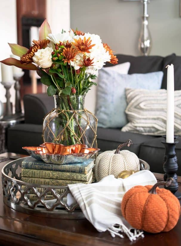 Coffee Table Fall decor vingette featuring flowers, pumpkins, candles, and old books.