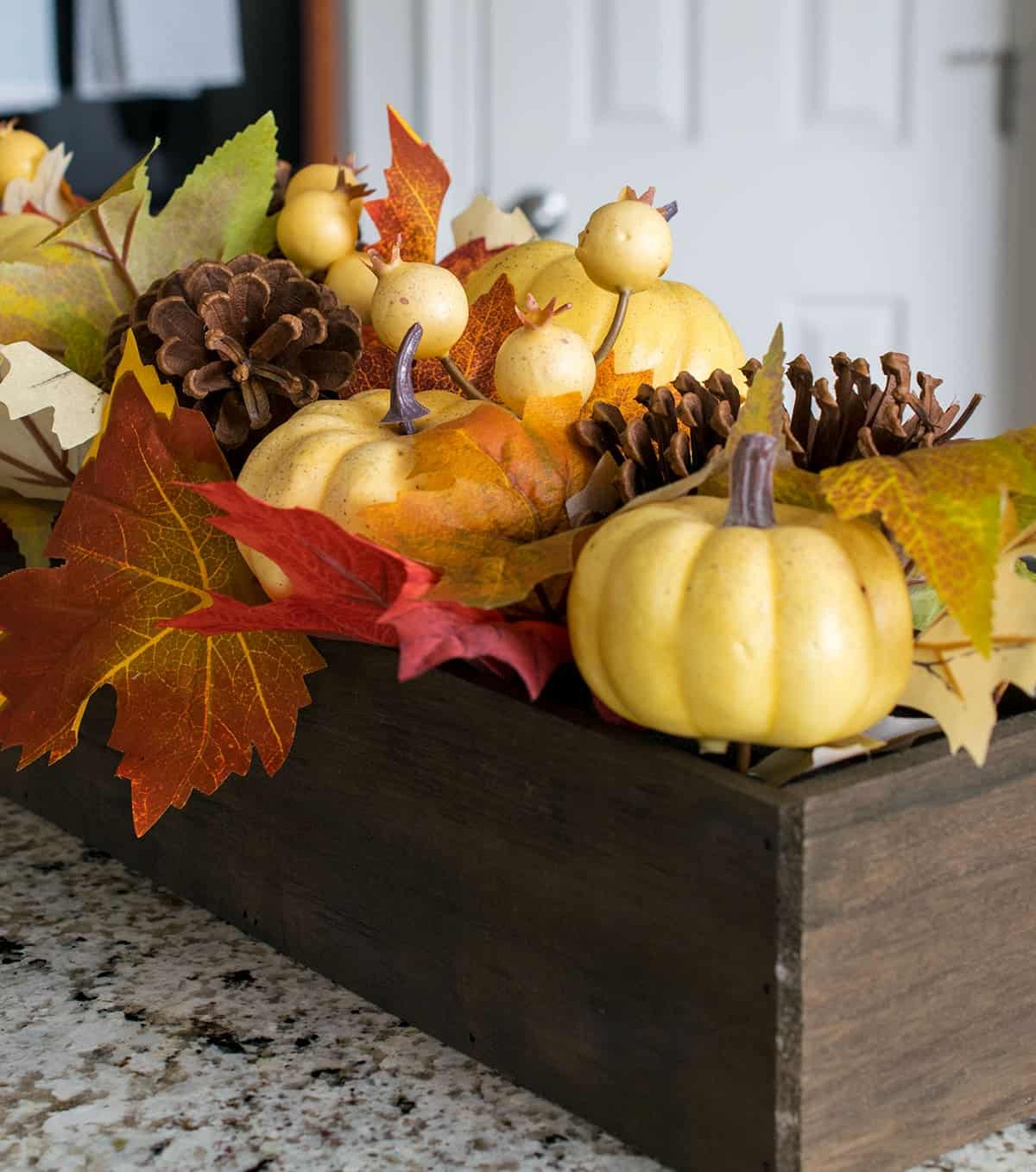 Fall inspired centerpiece on breakfast bar with small pumpkins, pinecones, and artificial autumn leaves.