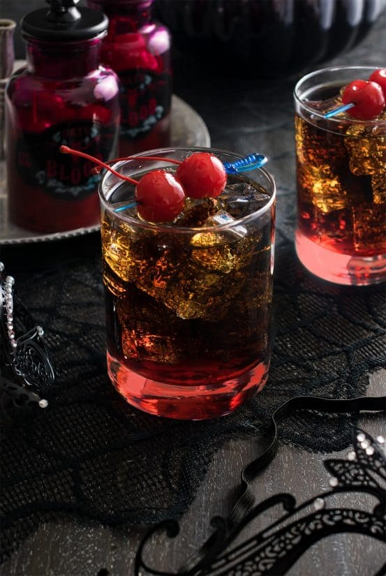 Two glasses of rum and coke over ice with a maraschino cherry garnish.