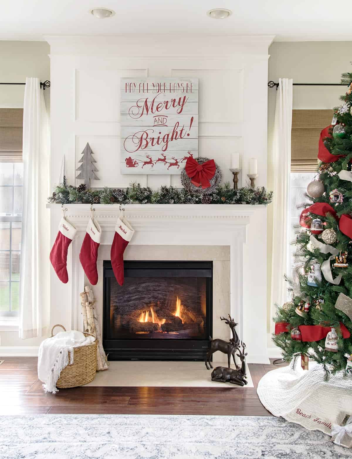 Traditional Christmas mantle and living room decor with garland, stockings and Christmas tree.