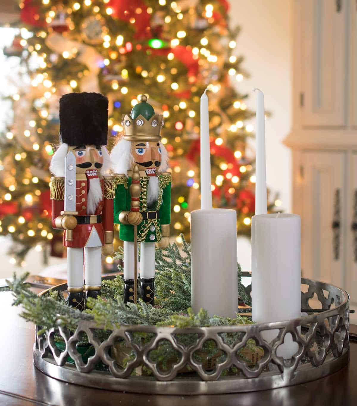 Nutcracker and candle sticks coffee table centerpiece idea with greenery.
