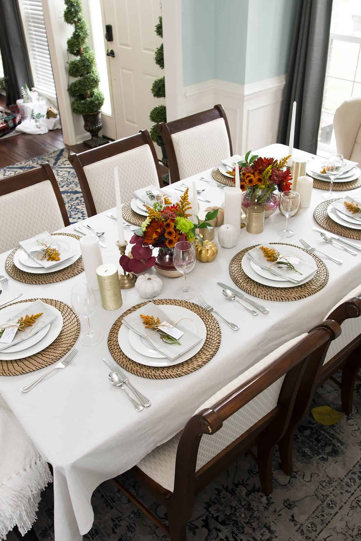 Overhead view of simple Thanksgving tablescape with neutral palette and natural elements.