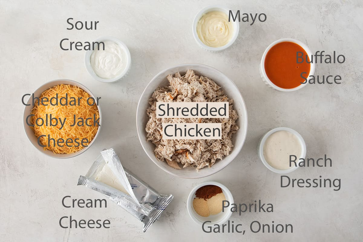 Ingredients for buffalo chicken dip laid out with text labels.
