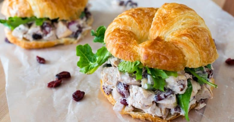 Cranberry Chicken Salad on a Croissant with greens and lunch wrap paper.