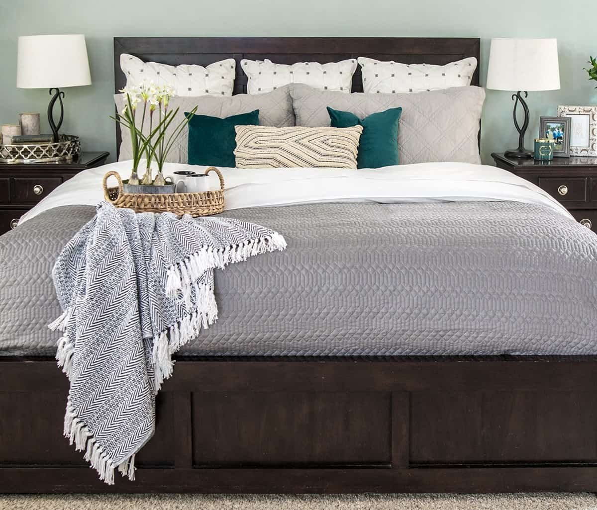 Cozy bed with gray quilt over white sheets. Layered neutral accent pillows with pops of green.
