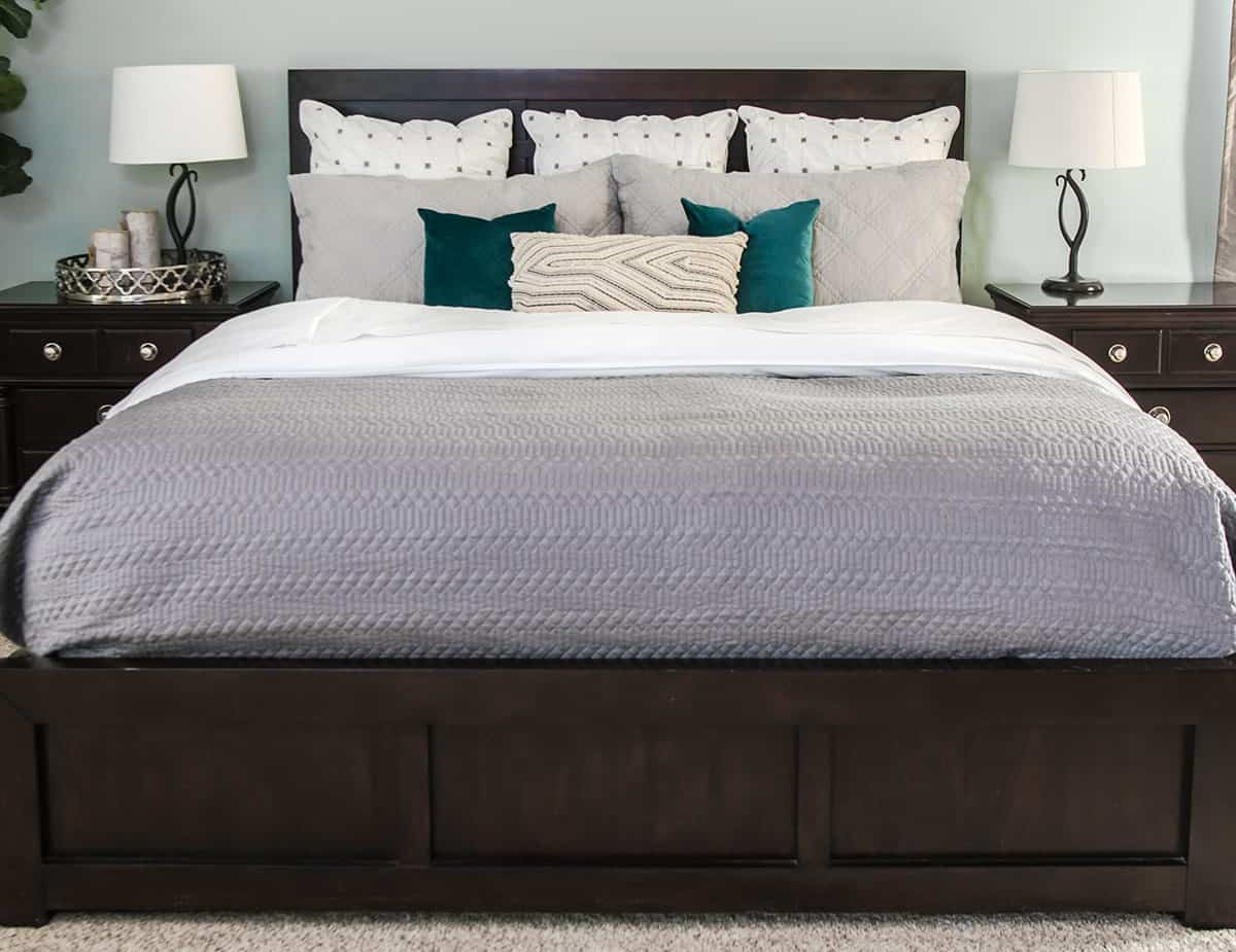 How to Make a beautiful bed final with Gray quilt, decorative throw pillows, shams, white sheets down turned.
