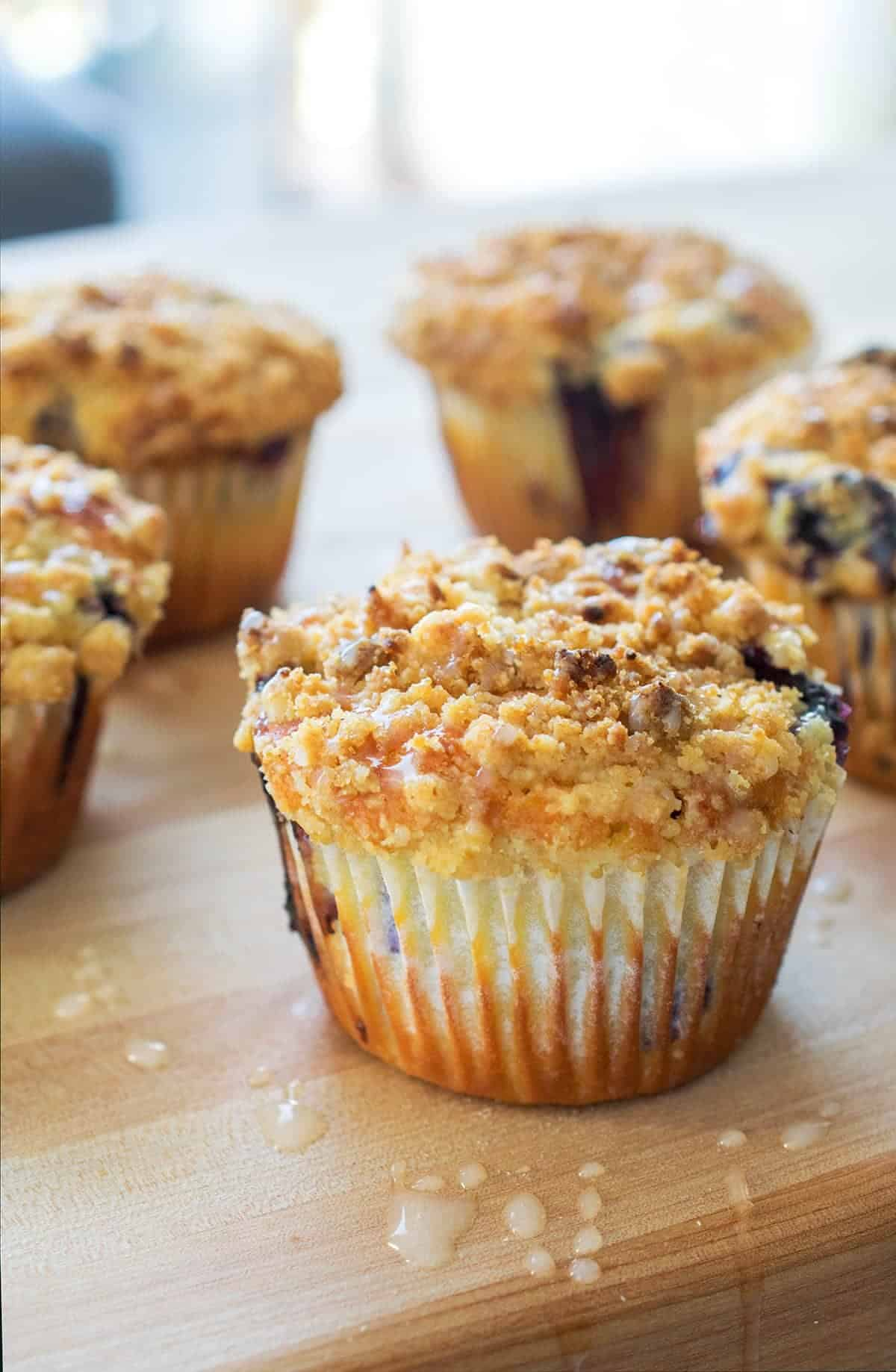 Lemon blueberry muffins with crumb topping on wood surface with sugar drips.