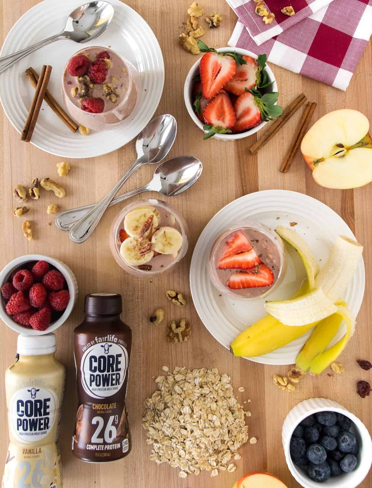 Ingredients for overnight oats on table including protein milk, fruit, oats, spoons, cinnamon.