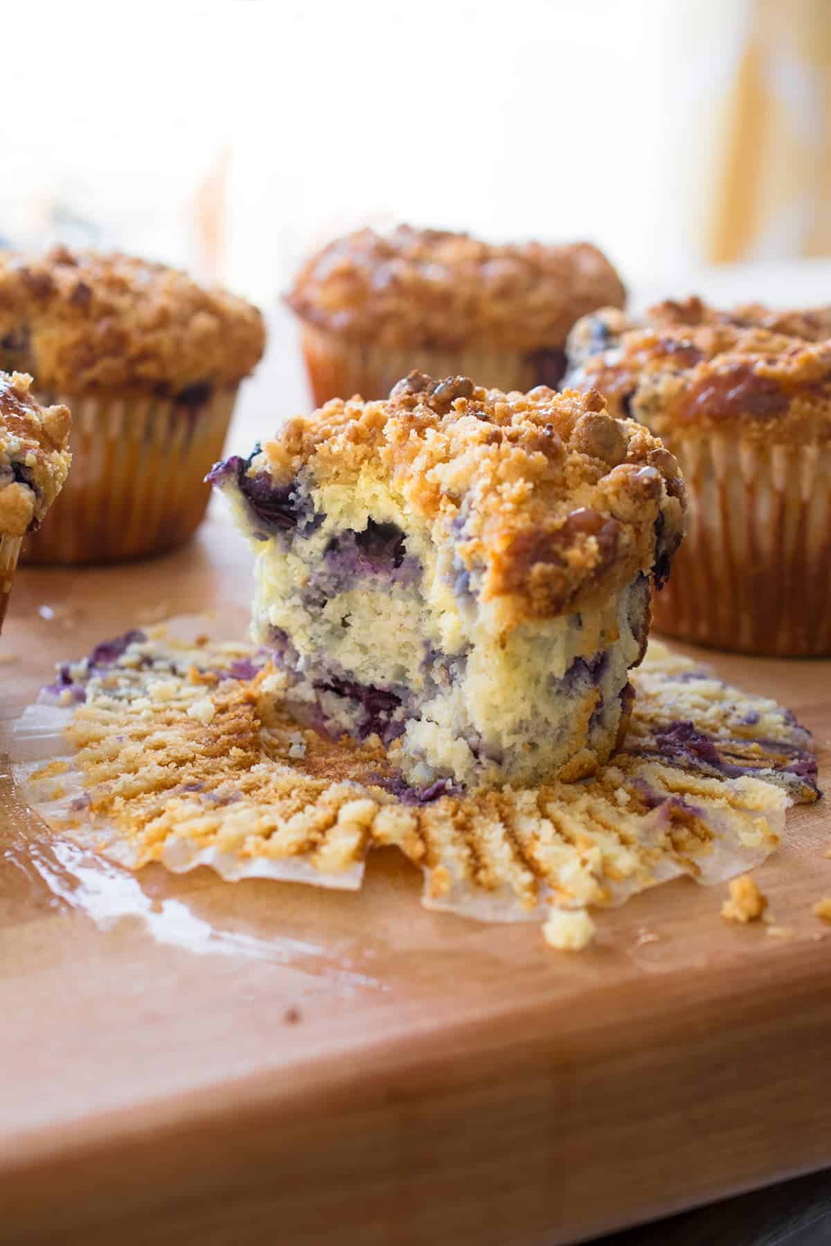 Lemon blueberry muffin with bite missing. 3 other muffins in the background.