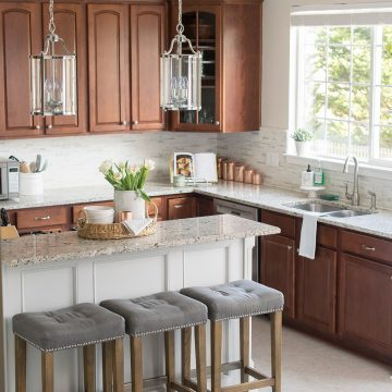 Traditional Kitchen Decorating and Remodel. This grey kitchen includes white granite, dark cabinets, marble backsplash, and a two level island.