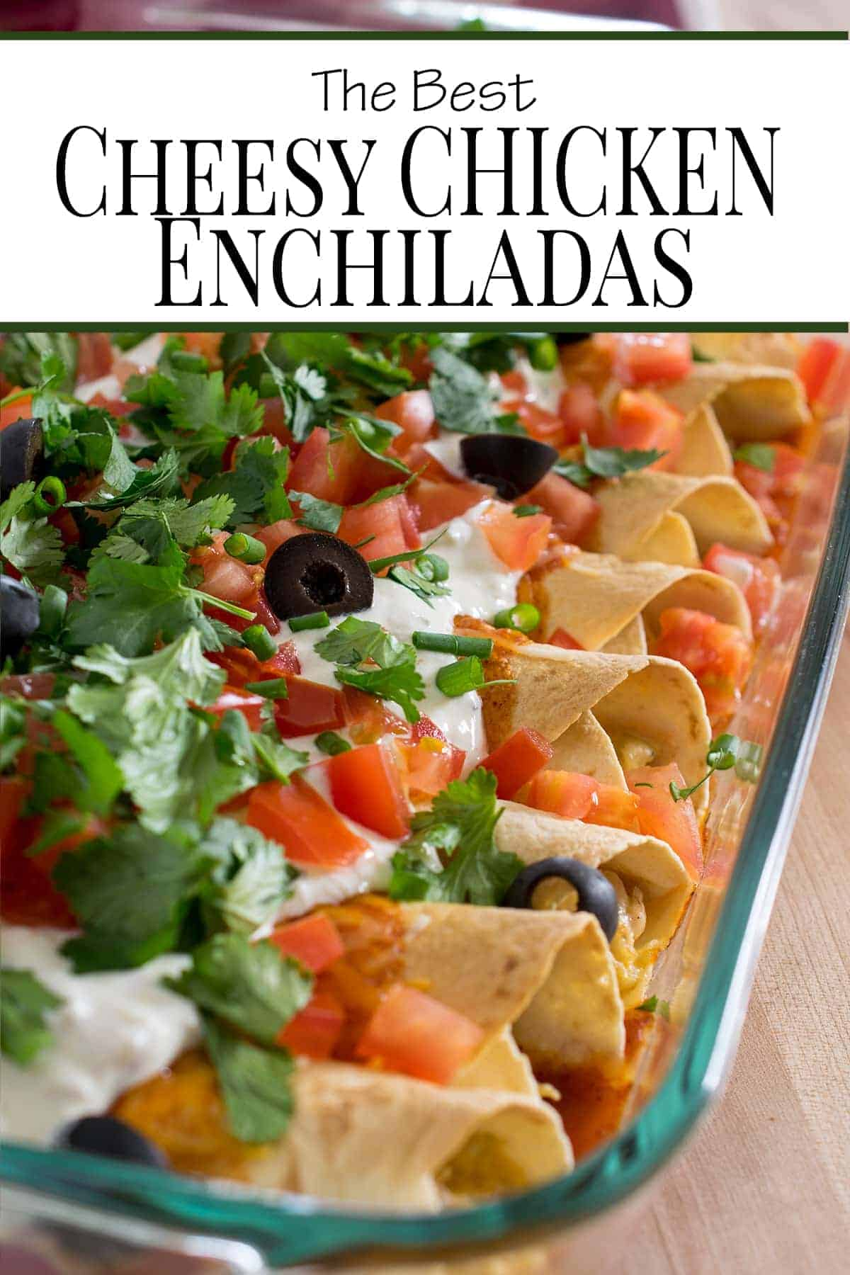 Chicken enchiladas topped with sour cream, pico de gallo, olives and sour cream in baking dish.