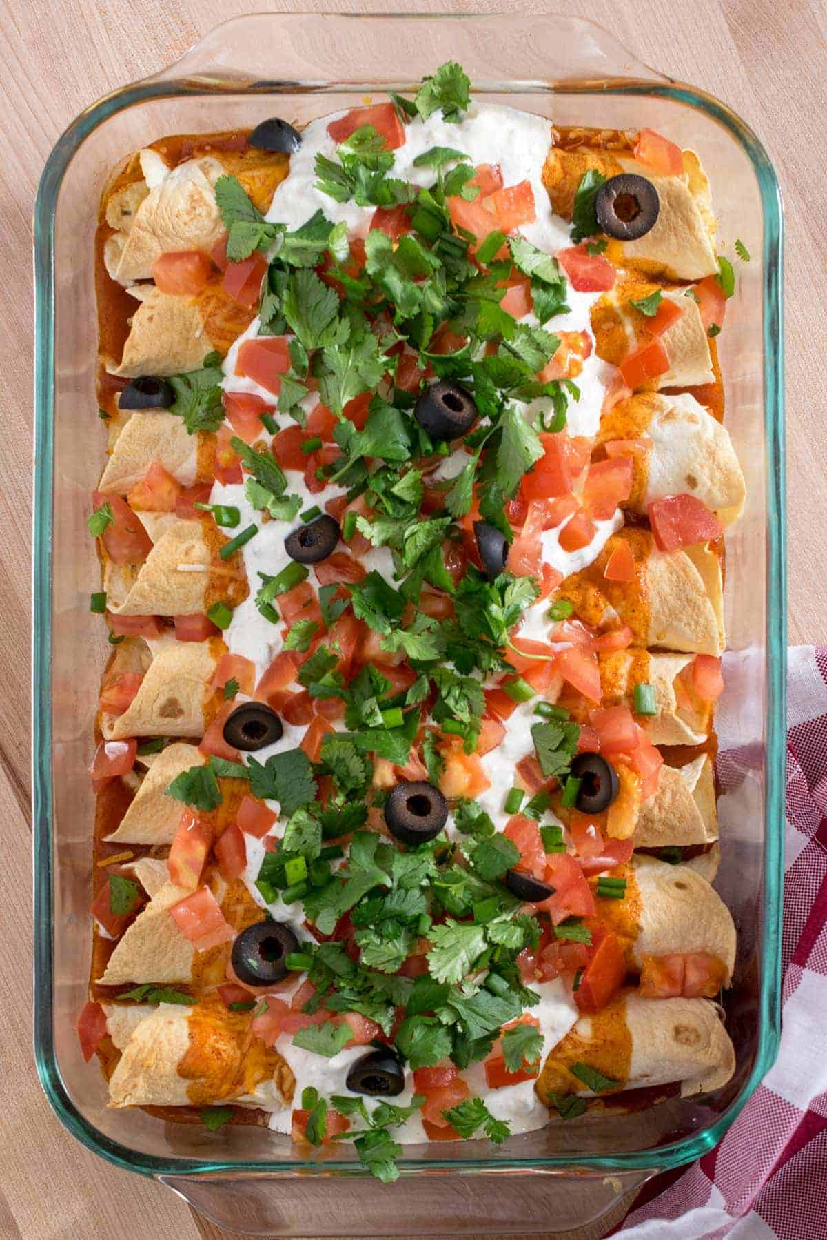 Aerial view of baked chicken enchiladas with sour cream, pico de gallo, olives, and cilantro in baking dish