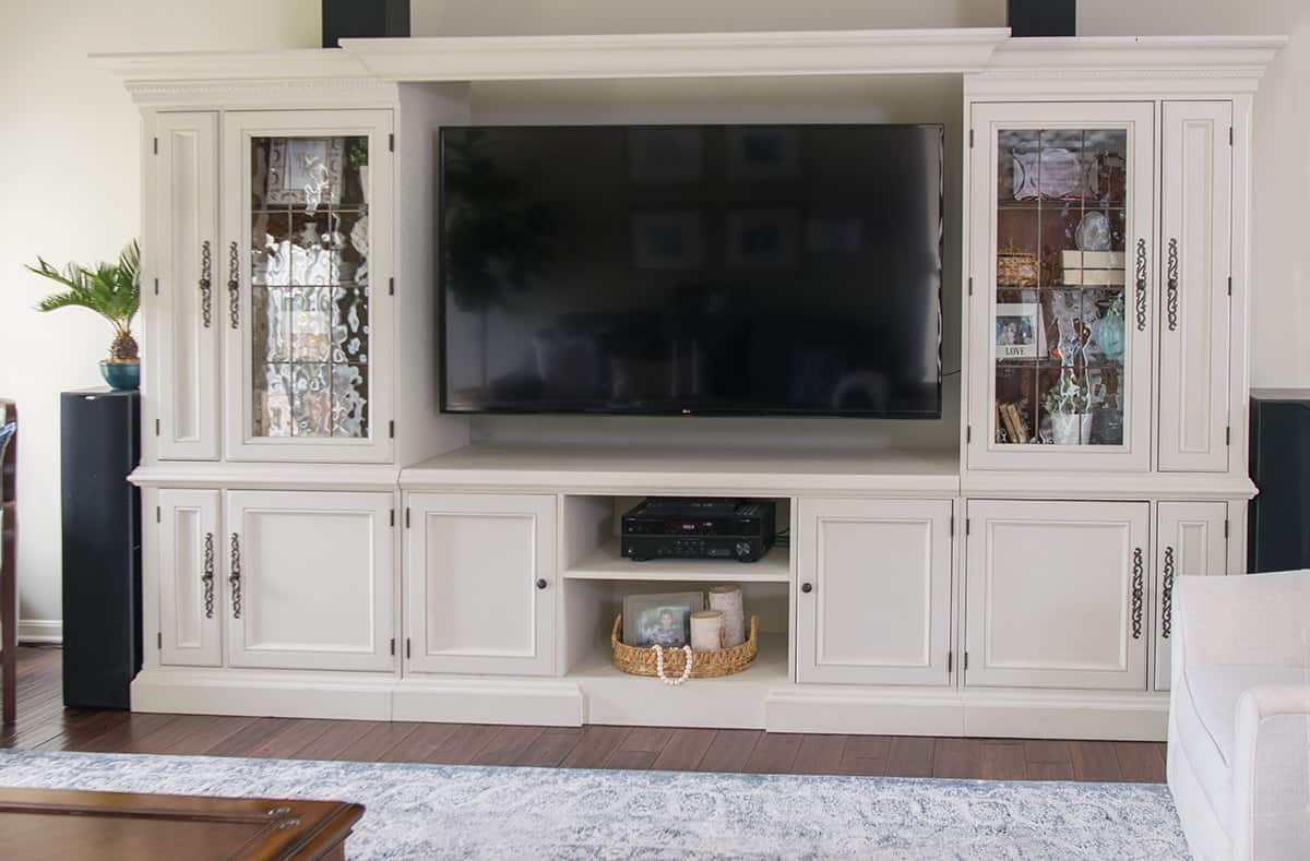 Traditional living room with global accents entertainment center makeover painted in cream.