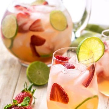 Sangria with strawberries and limes in a glass on a table with a pitcher in the background.