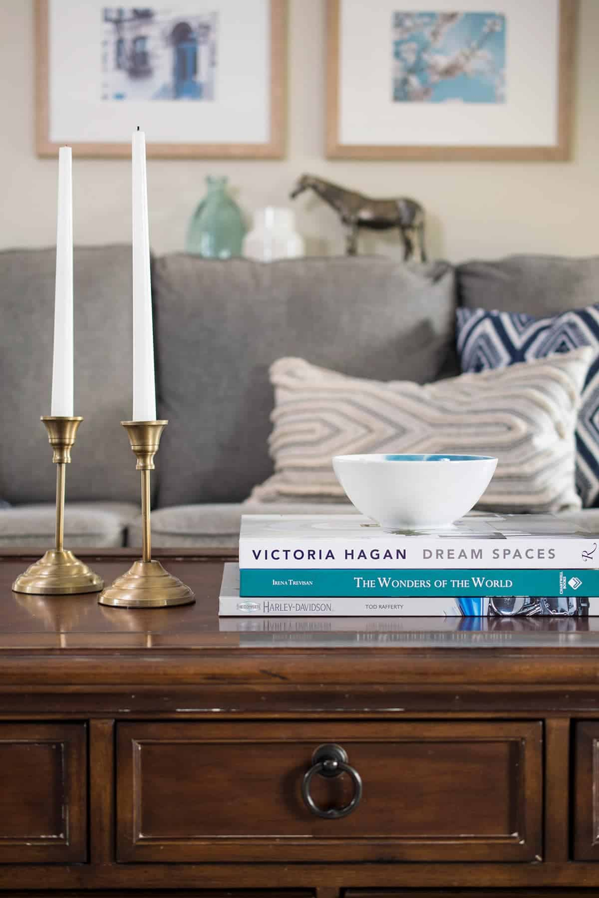 Coffee table styling close up includes books, brass candle sticks and decorative bowl.