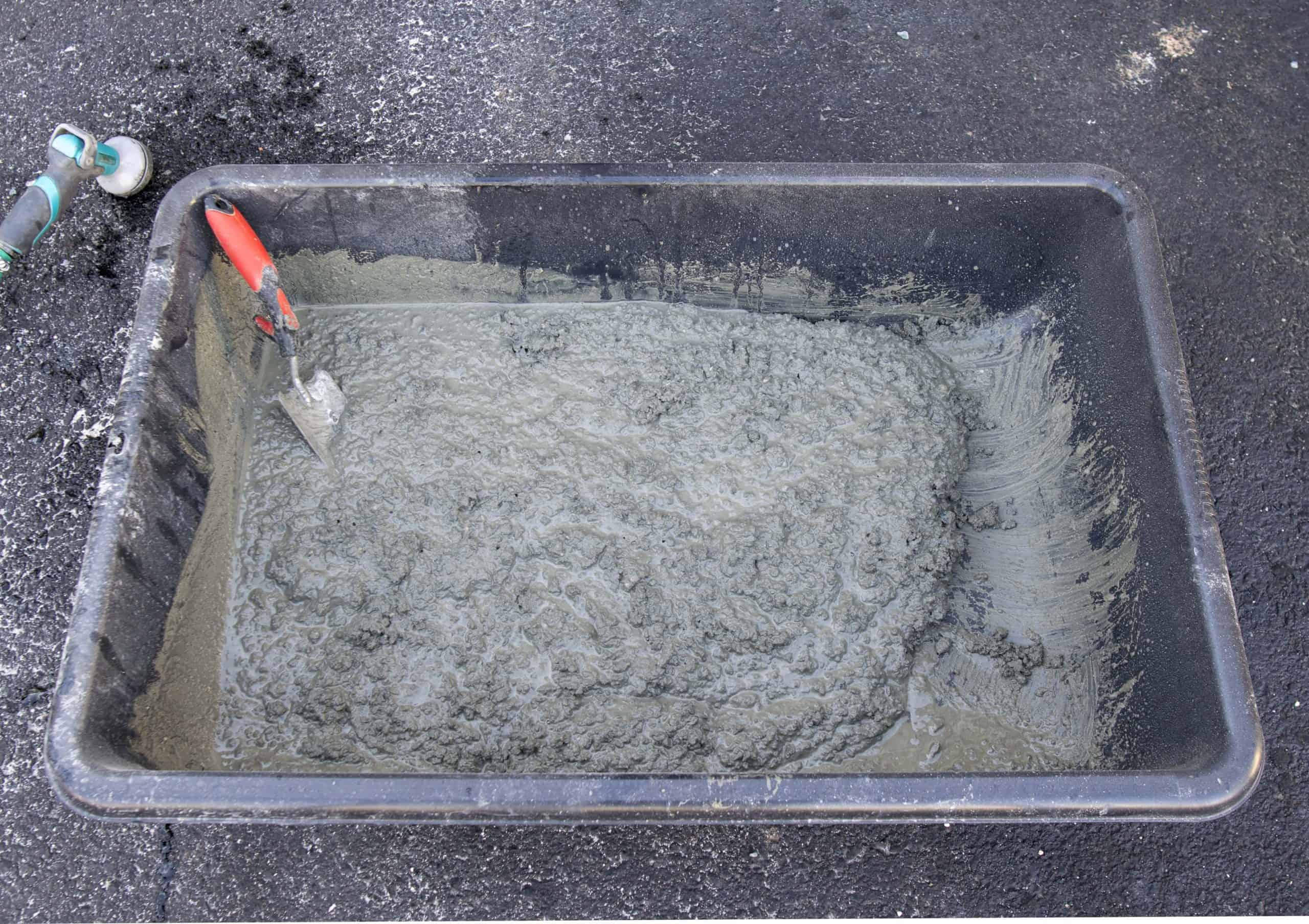 Mixed concrete with water in a trough with thick oatmeal consistency