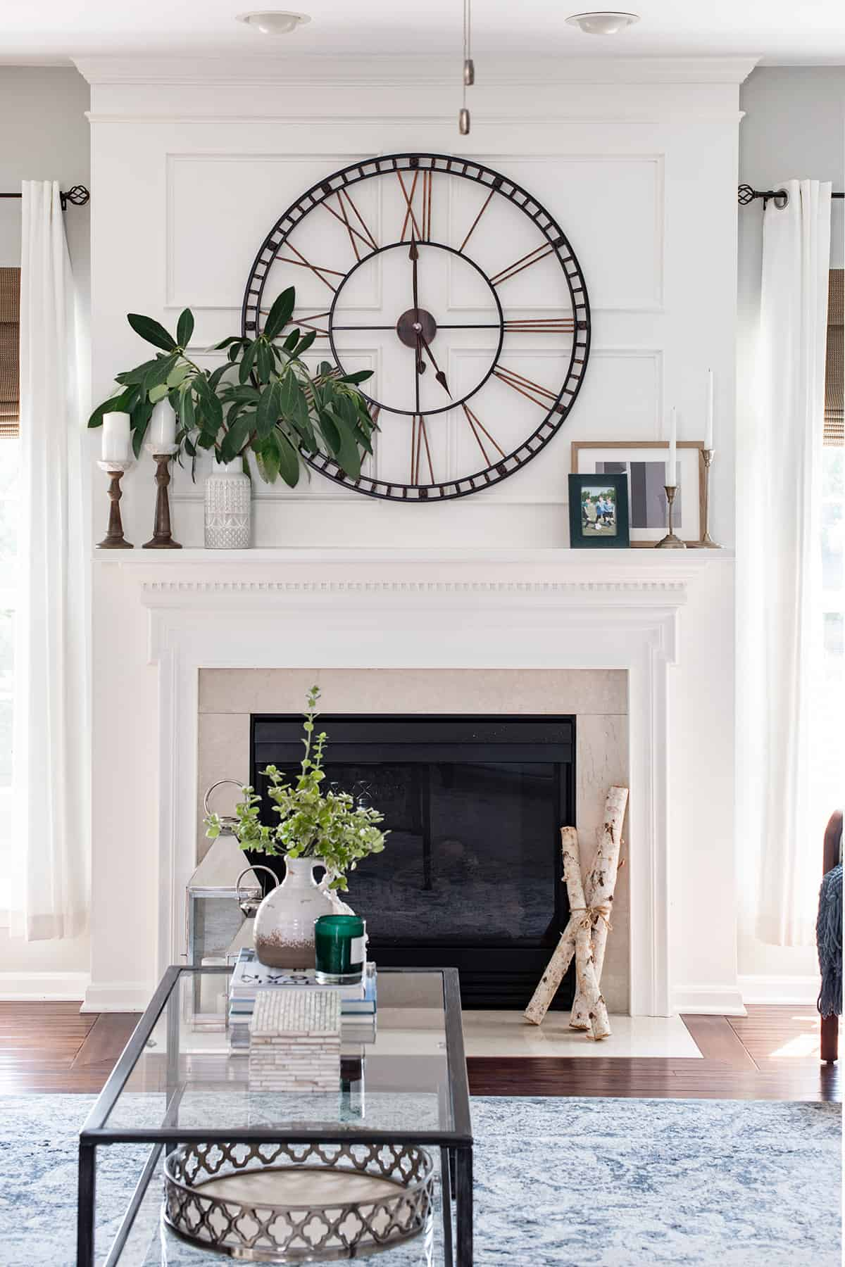 Fireplace mantle picture frame trim decoration with oversized clock.