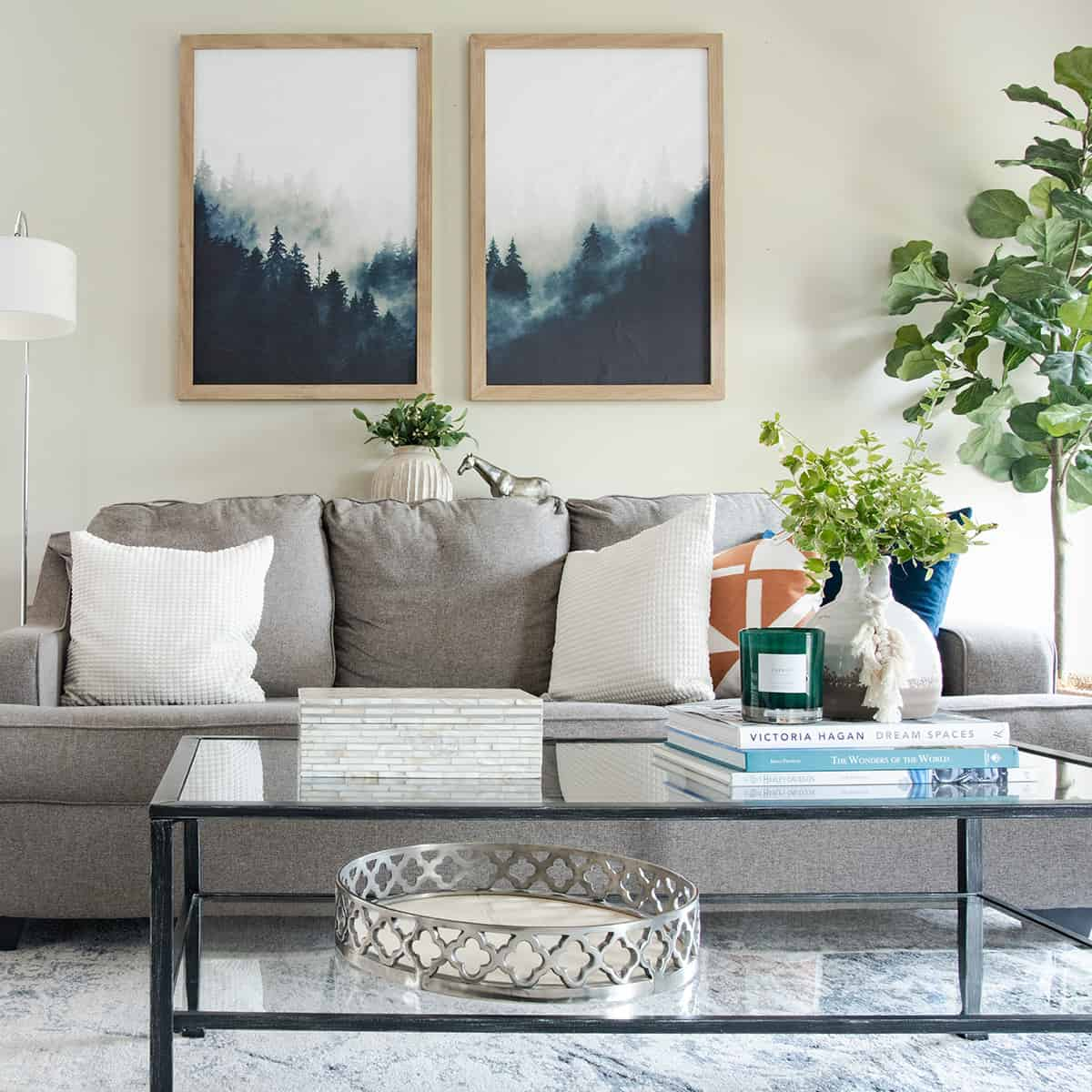 Light grey couch with colorful accents and glass coffee table filled with fresh greenery.