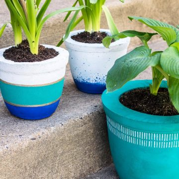 Three colorful planters made of concrete. A DIY project with painted pots.