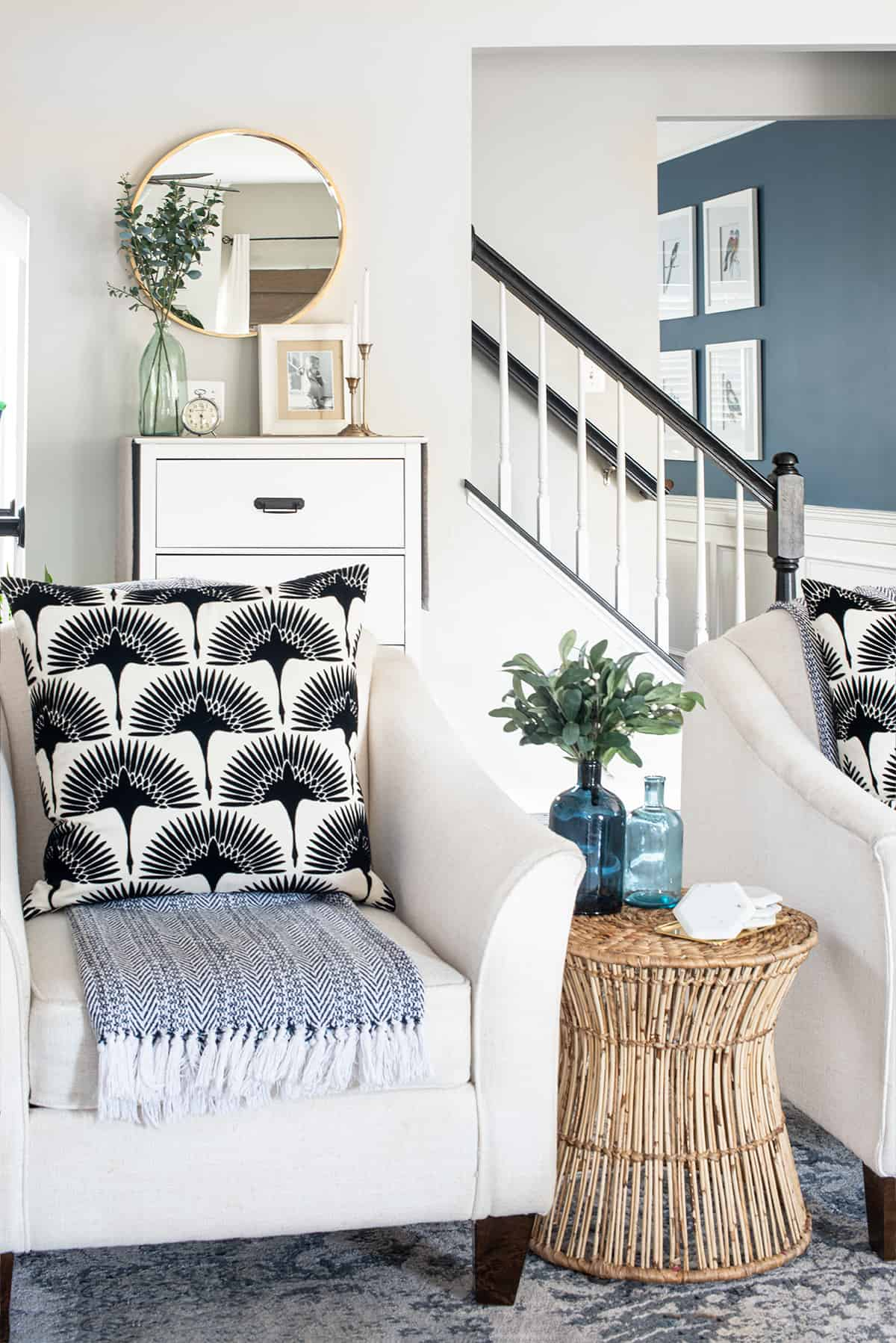 Two white accent chairs with bamboo side table in a bohemian and traditional style with staircase behind them.