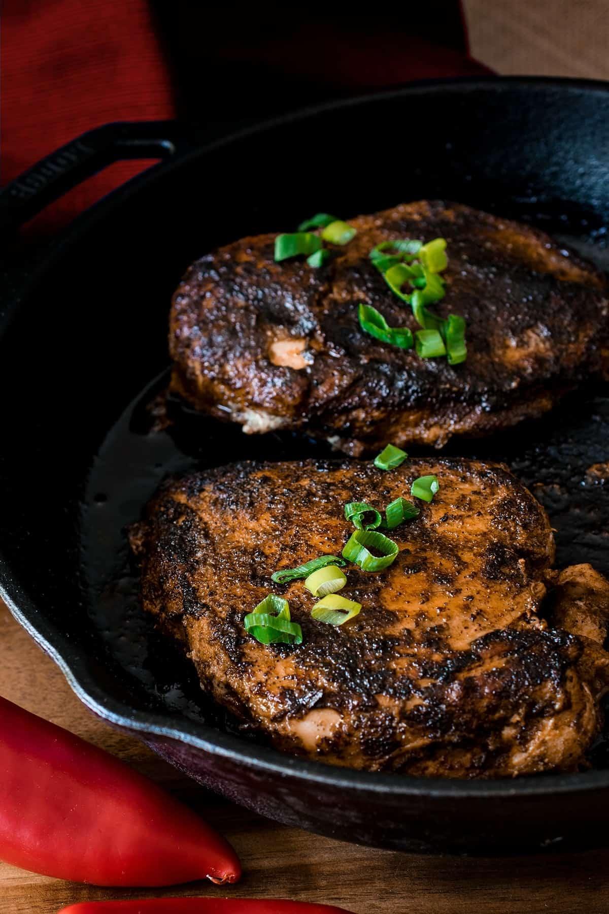 Cajun Blackened Chicken with garnish in a skillet.