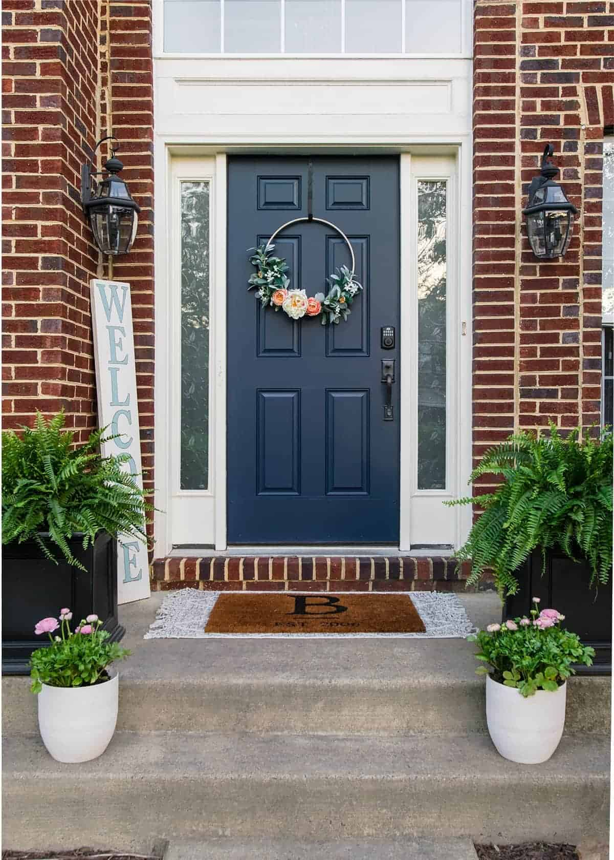 Front porch decor with blue front door, white accents against brick exterior. Layered door mats, potted ferns and DIY Welcome sign and planters.