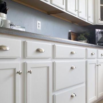White painted kitchen cabinets with stainless drawer pulls.