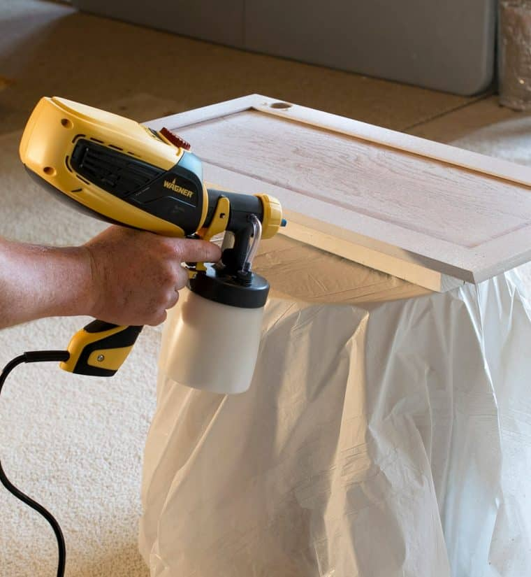 A paint sprayer being used to paint a cabinet door white.