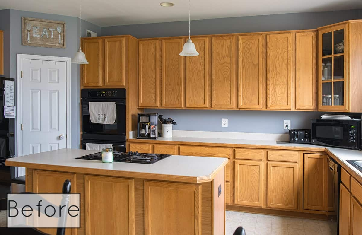Before photo of kitchen cabinets light oak with white countertops.