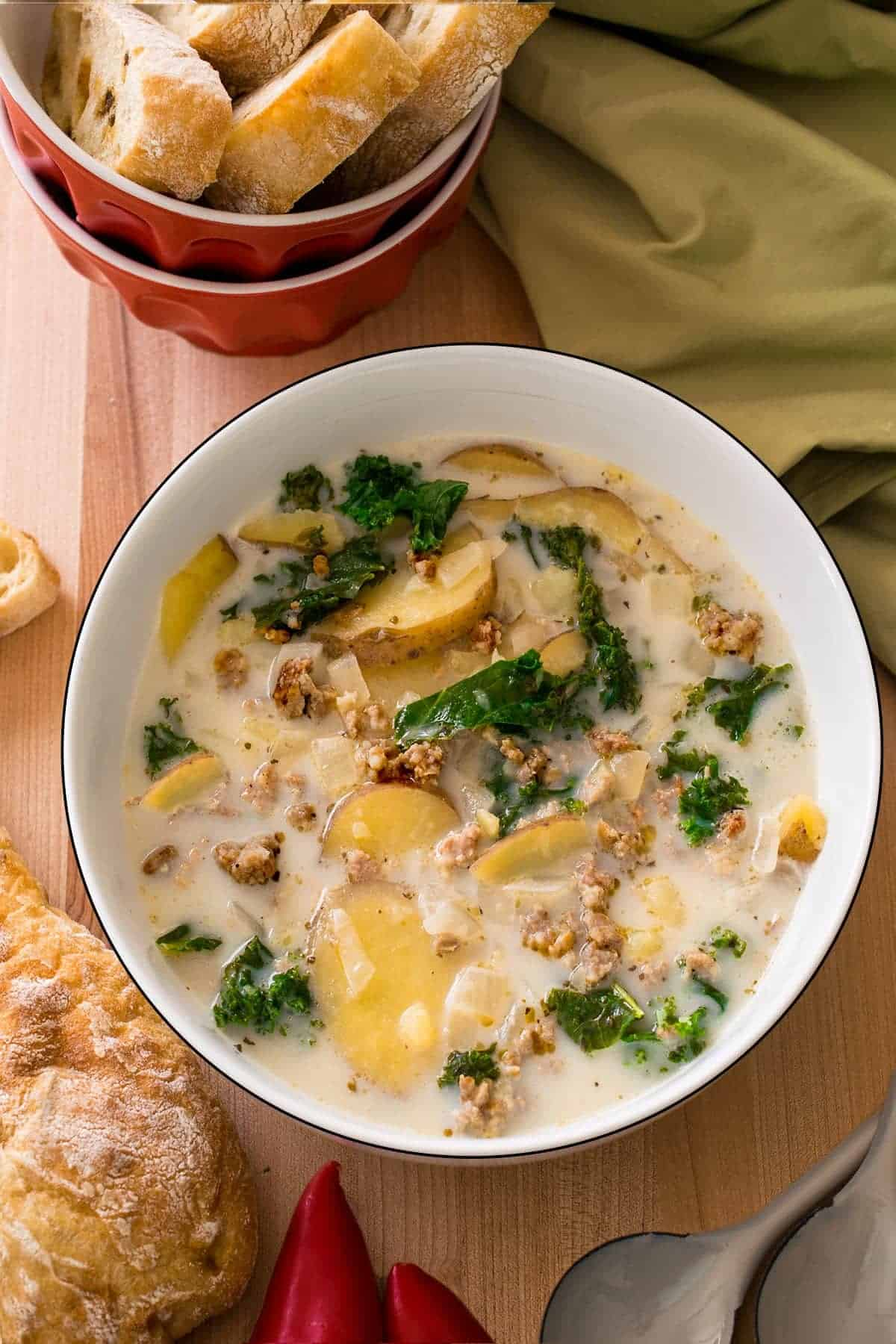 Italian sausage kale soup in white bowl on cutting board with crusty bread on the side and red bowl of crusty bread slices behind.